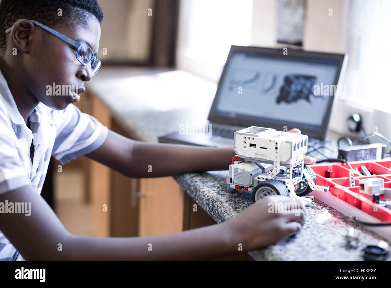 Scolaro con il computer portatile nella classe di robotica Immagini Stock