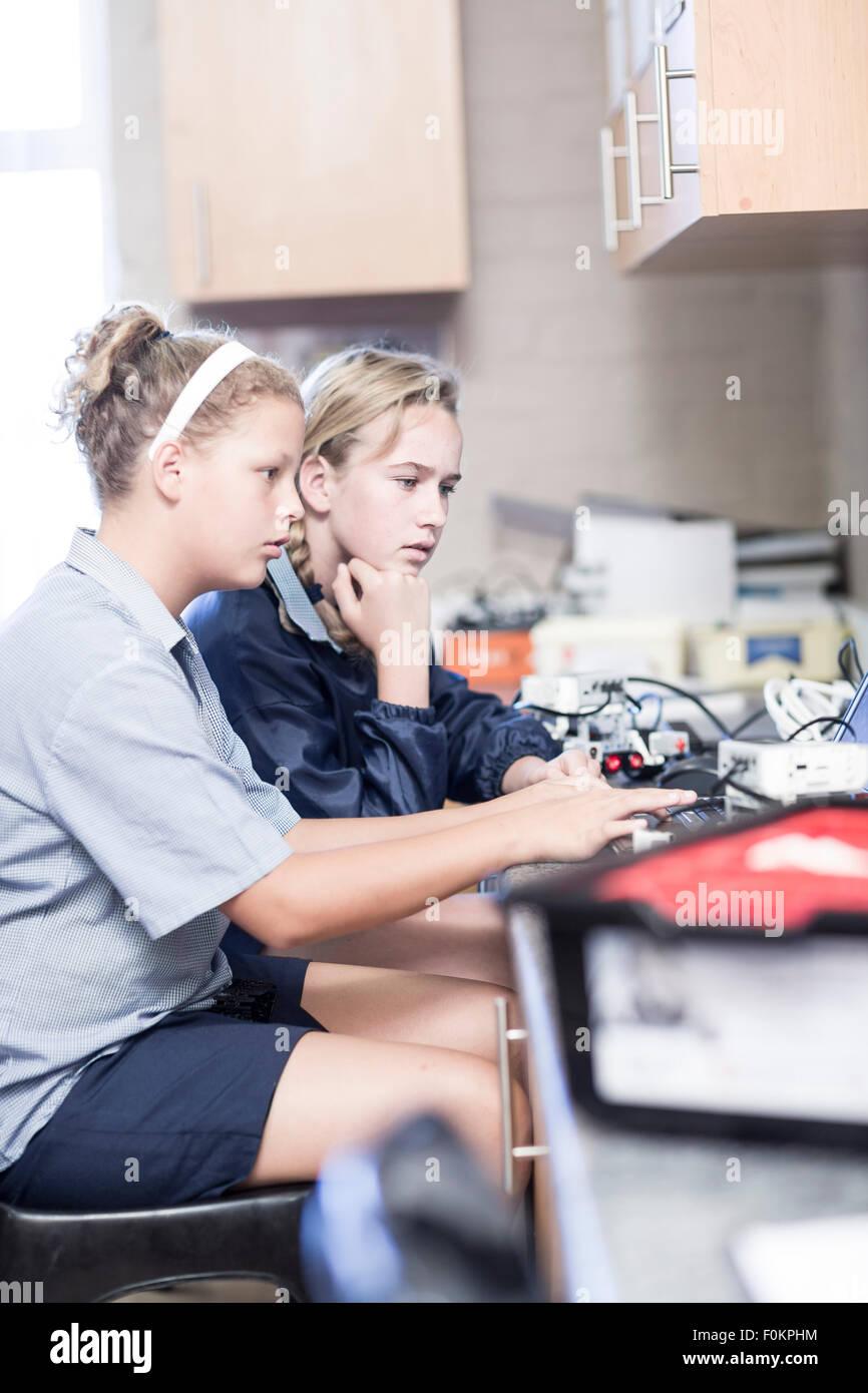 Due studentesse con il computer portatile nella classe di robotica Immagini Stock