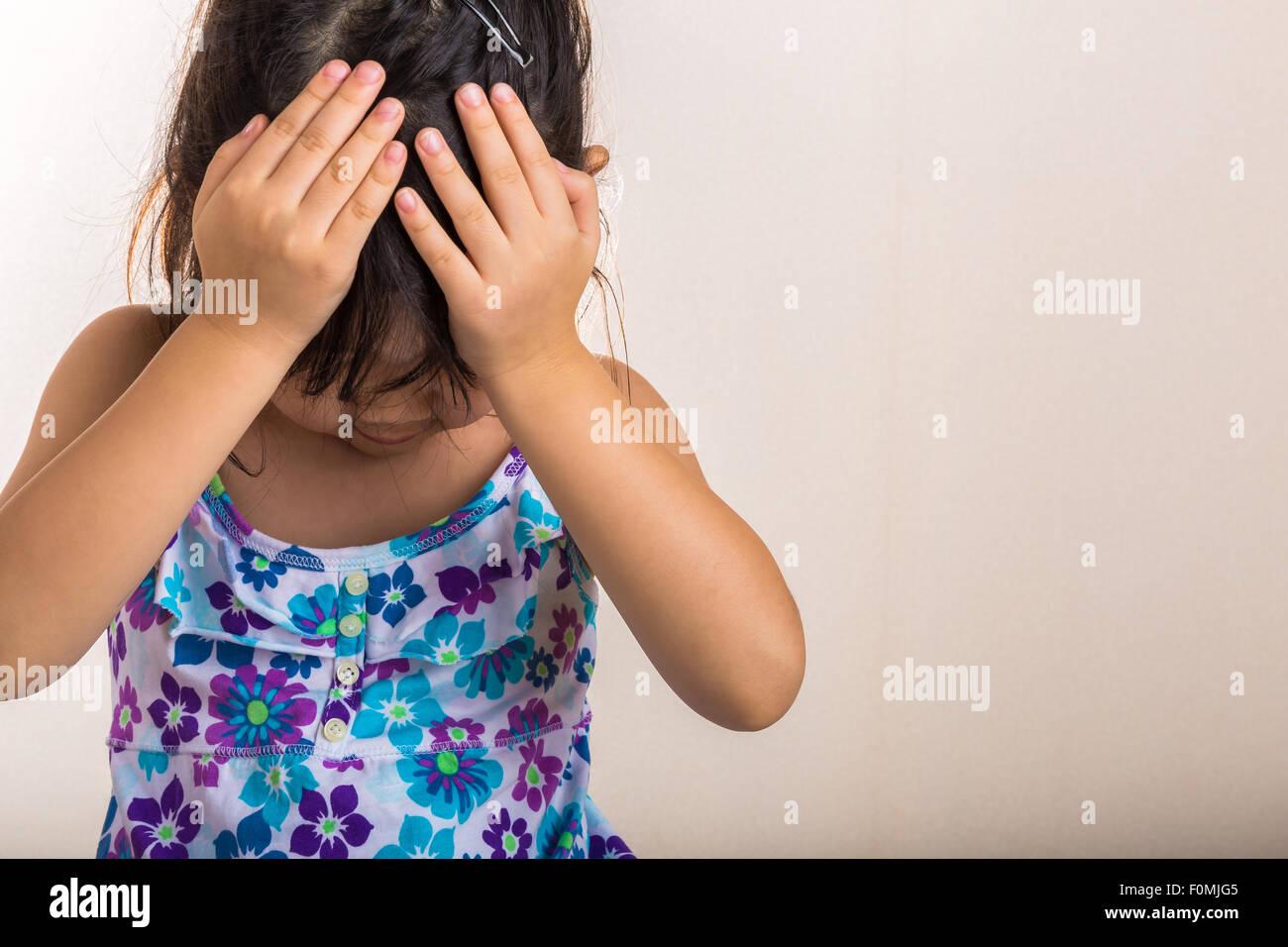 Bambina copre la fronte con le mani quando sentirsi deluso. Immagini Stock