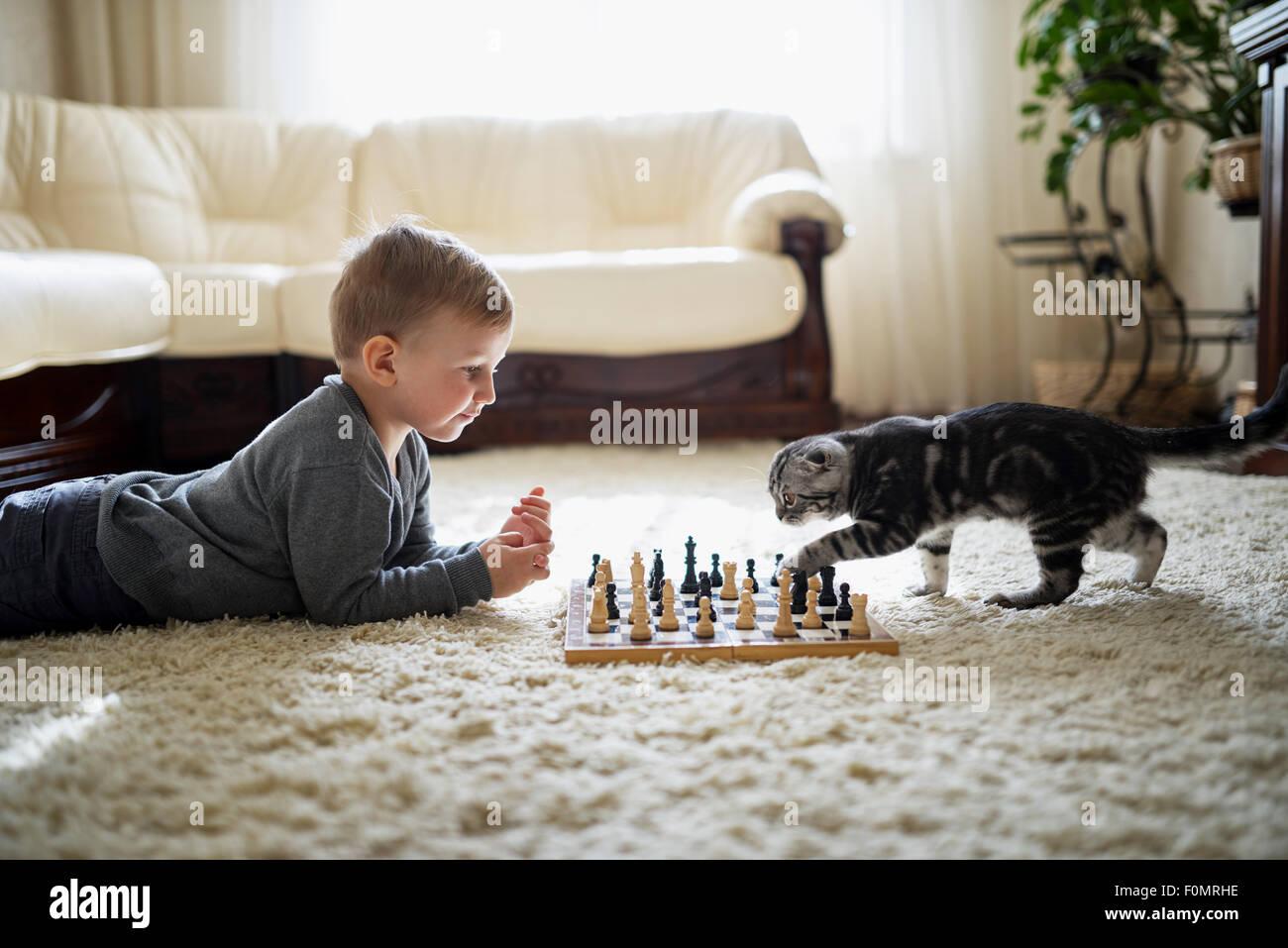 Little Boy gioca a scacchi sdraiato sul pavimento Immagini Stock