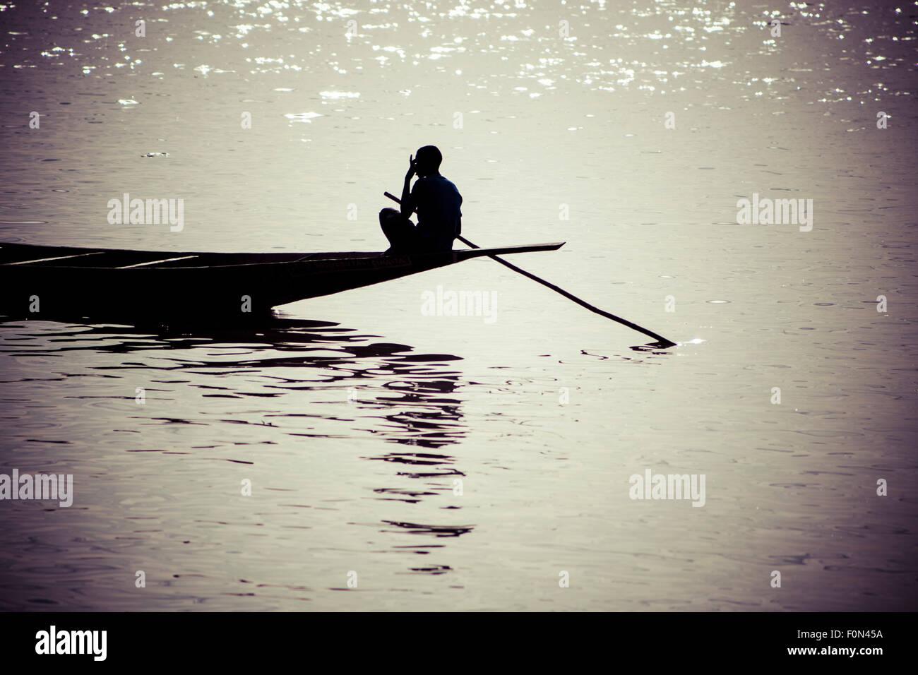 Irriconoscibile la silhouette di un giovane ragazzo nero seduto su una piccola imbarcazione sul Fiume Niger in Mali, Foto Stock