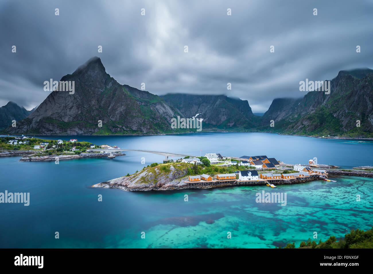 Montare Olstind sopra le cabine gialle e turquise acque di Sakrisoy nei villaggio di pescatori sulle isole Lofoten Immagini Stock