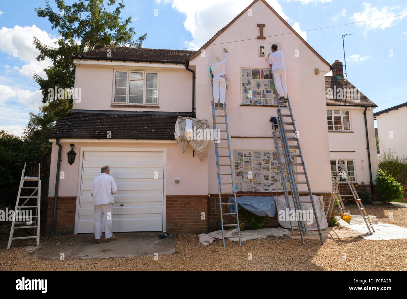 Casa professionale pittori pittura la parte esterna di una casa, Suffolk, East Anglia England Regno Unito Immagini Stock