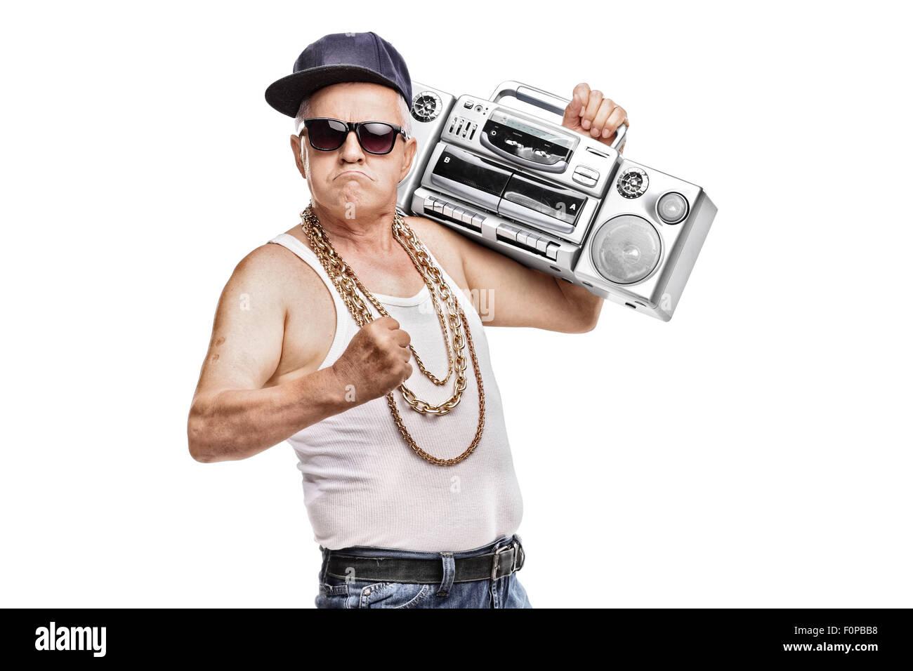 Uomo maturo in hip-hop outfit tenendo un ghetto blaster e guardando la telecamera  isolata su sfondo bianco a7b7b1629eed