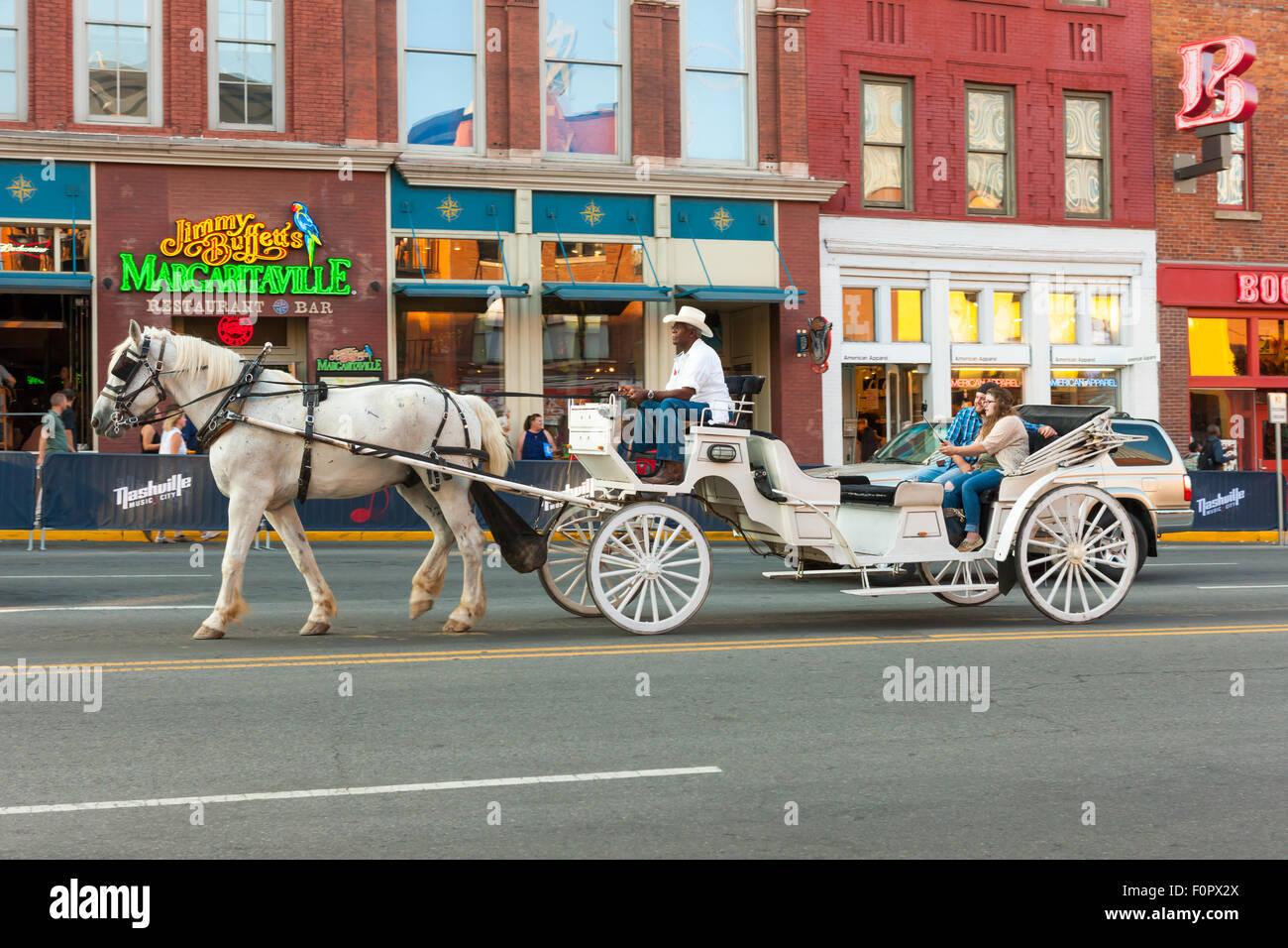 Un giovane prende un selfie mentre in sella a una carrozza trainata da cavalli verso il basso Broadway a Nashville, Immagini Stock