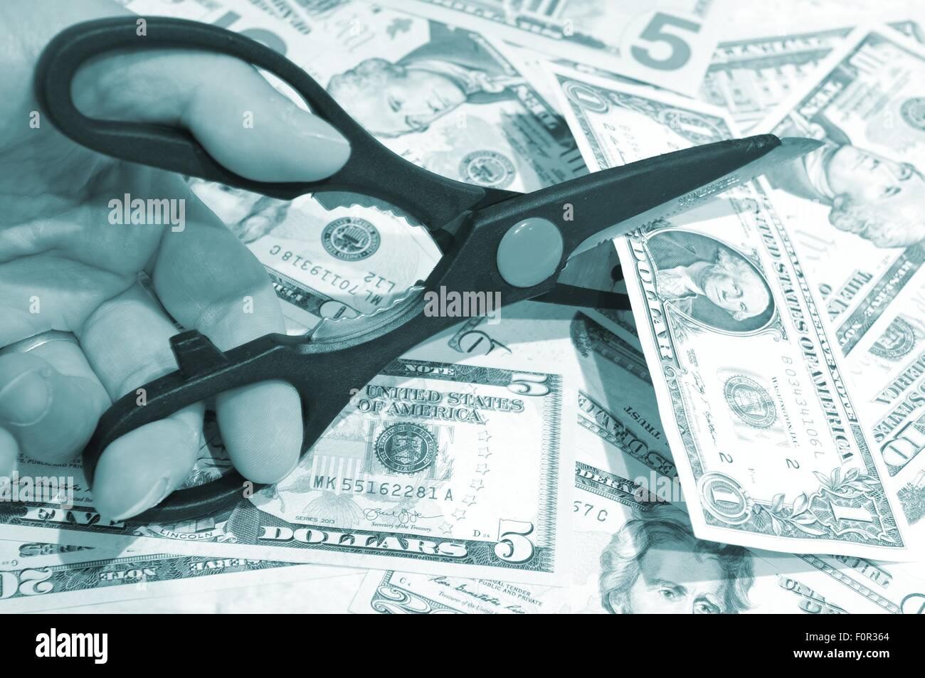 Tagli di bilancio concetto con forbici e Dollari USA Immagini Stock
