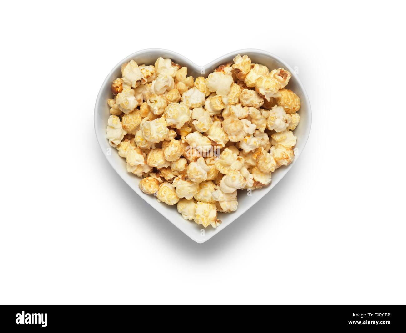 Colpo di stile cinema popcorn in un cuore ciotola sagomata isolata su uno sfondo bianco con un tracciato di ritaglio e copia dello spazio per la d Foto Stock