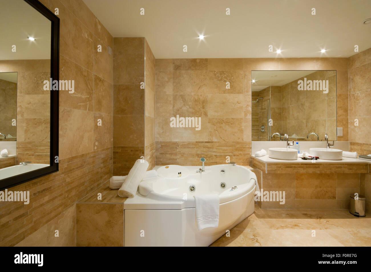 Moderno bagno interno con piastrelle di marmo e specchio foto