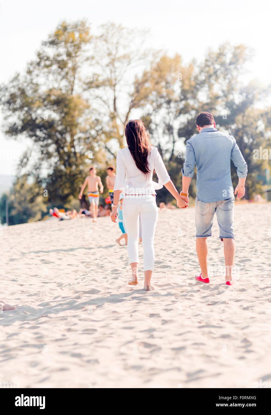 Giovane tenendo le mani e piedi su di una spiaggia di sabbia Immagini Stock
