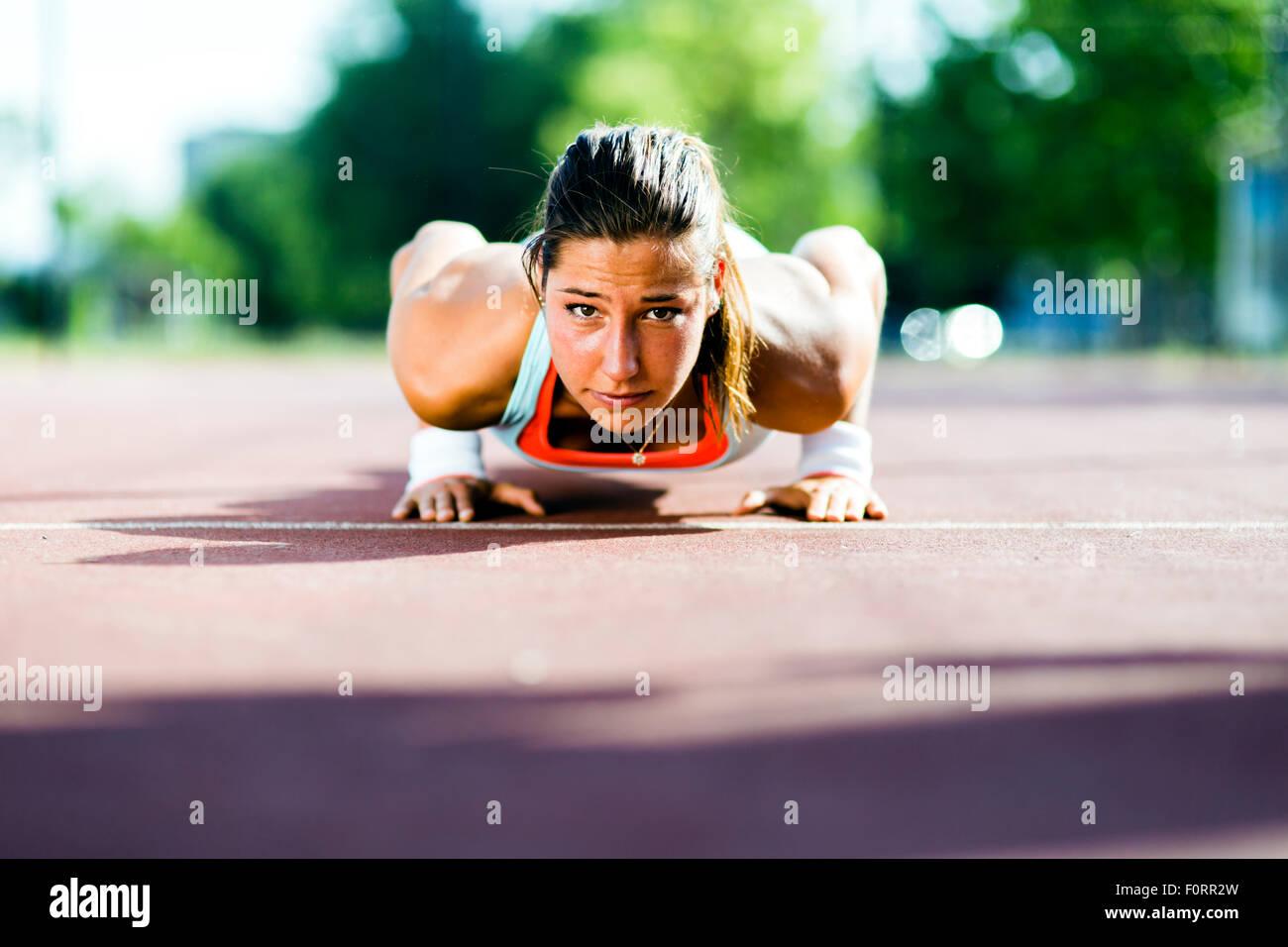 Focalizzato giovane bella donna facendo push-up all'aperto in una calda giornata estiva Foto Stock