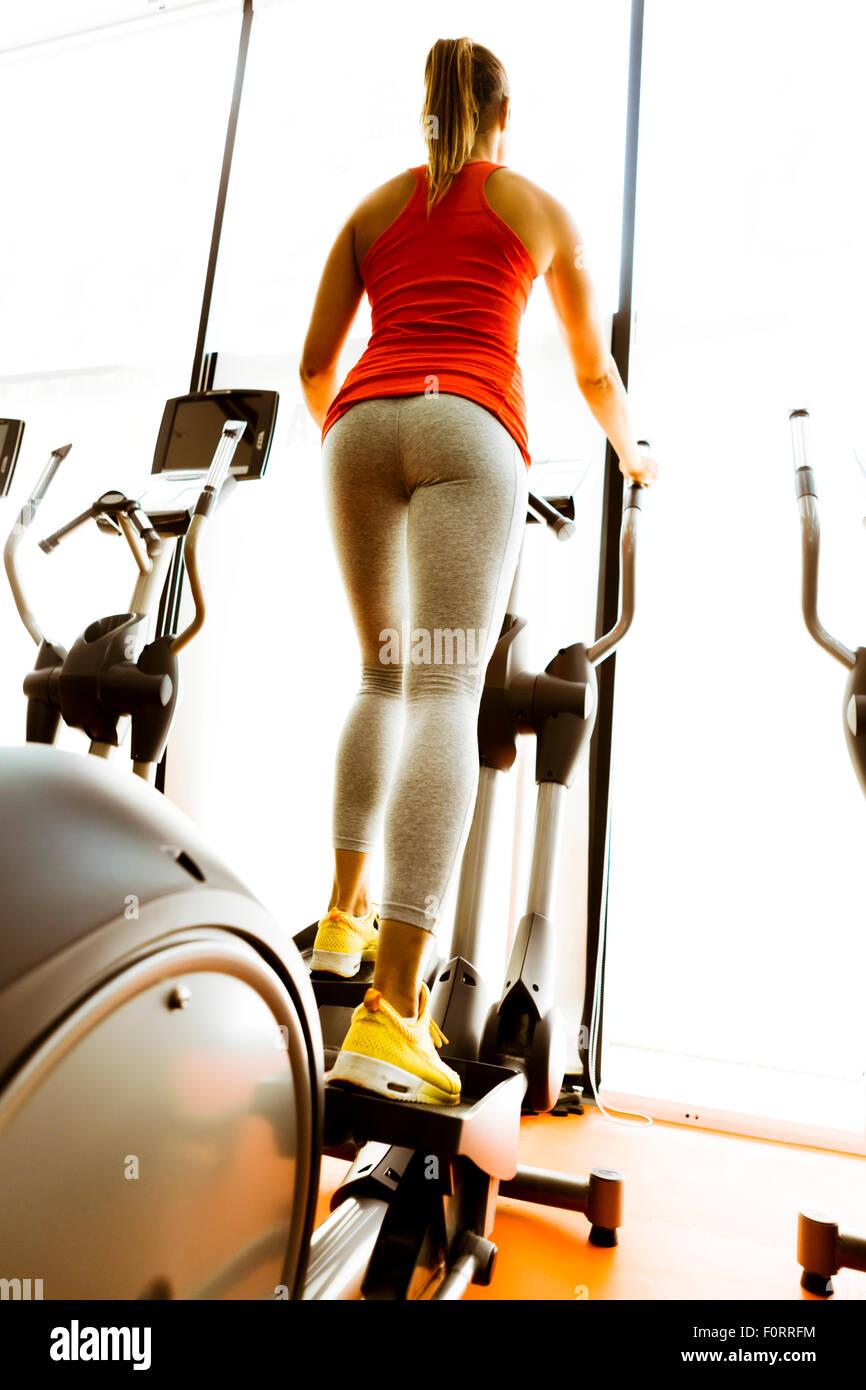 Primo piano di una donna utilizzando uno stepper e la formazione in un centro fitness Immagini Stock