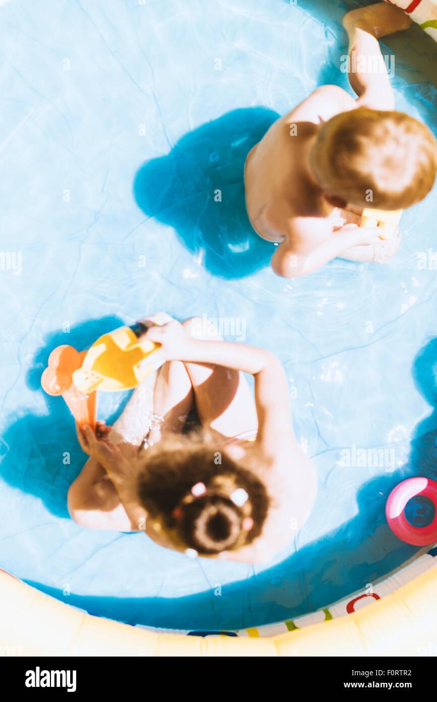 Giovani bambini che giocano con giocattoli in una piscina gonfiabile durante l'estate Immagini Stock