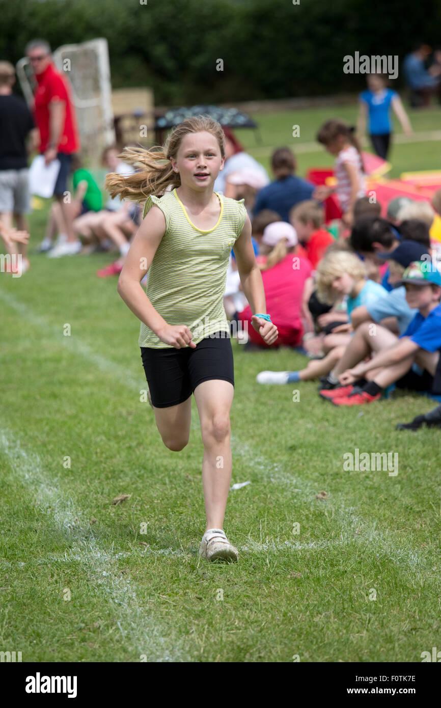 Ragazza che corre nella gara sprint Scuola di sport giorno Chipping Campden Regno Unito Immagini Stock