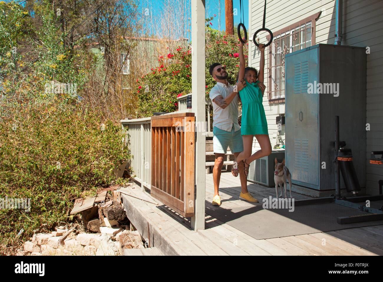 Metà uomo adulto figlia di sollevamento su esercizio gli anelli sul patio Immagini Stock
