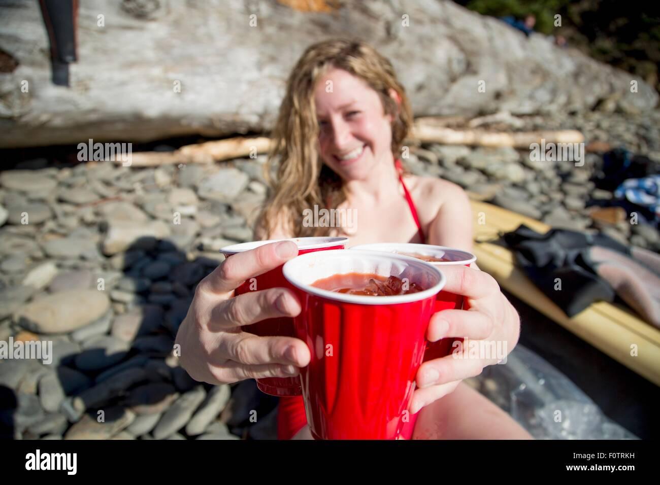 Giovane donna seduta sulla spiaggia rocciosa, tenendo le bevande, sorridente, breve Sands Beach, Oregon, Stati Uniti Immagini Stock