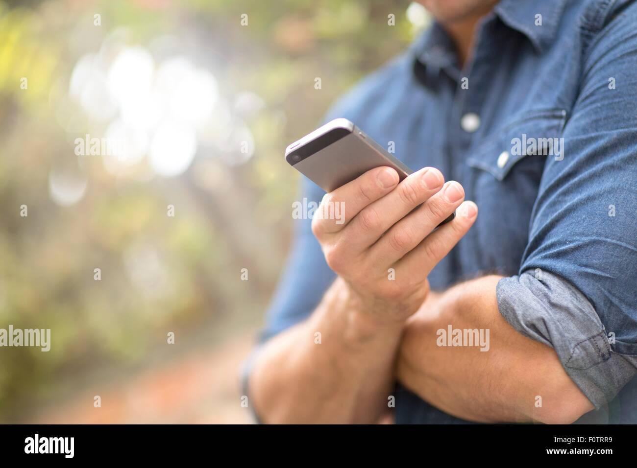 Metà uomo adulto, esterni tramite telefono cellulare, metà sezione Immagini Stock