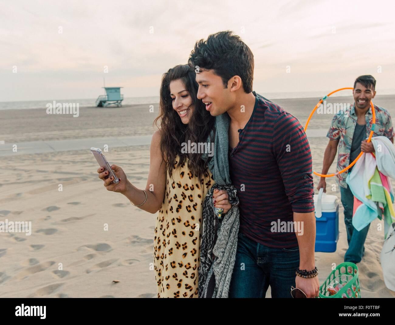 Gruppo di amici a piedi lungo la spiaggia, coppia giovane guardando smartphone Foto Stock