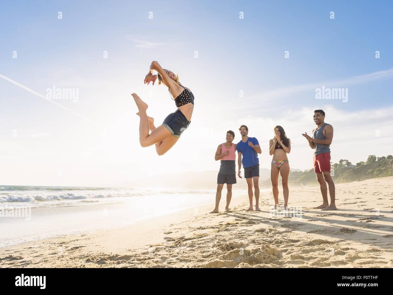 Gruppo di amici sulla spiaggia per guardare un amico salto in aria Foto Stock