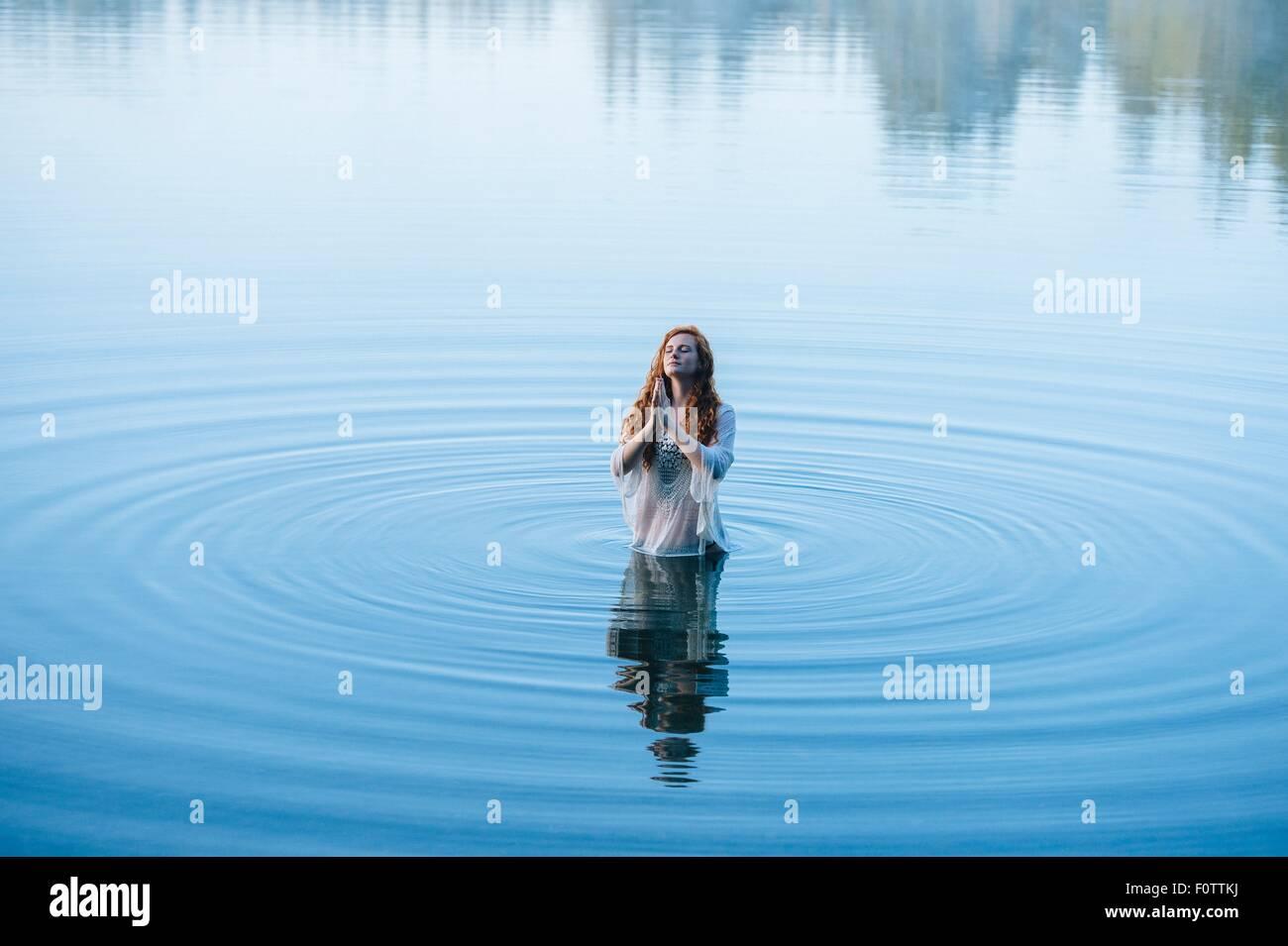 Giovane donna in piedi nel lago di increspature pregando con gli occhi chiusi Immagini Stock