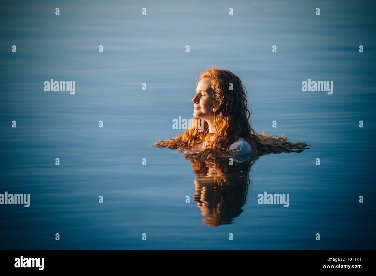 La testa e le spalle del giovane donna con lunghi capelli rossi nel lago con gli occhi chiusi Immagini Stock