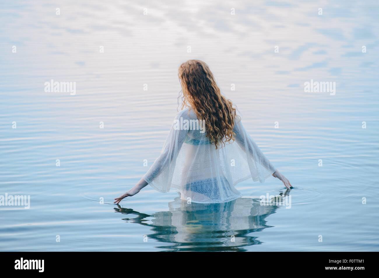 Vista posteriore della giovane donna in piedi nel lago increspa la superficie con le dita Immagini Stock