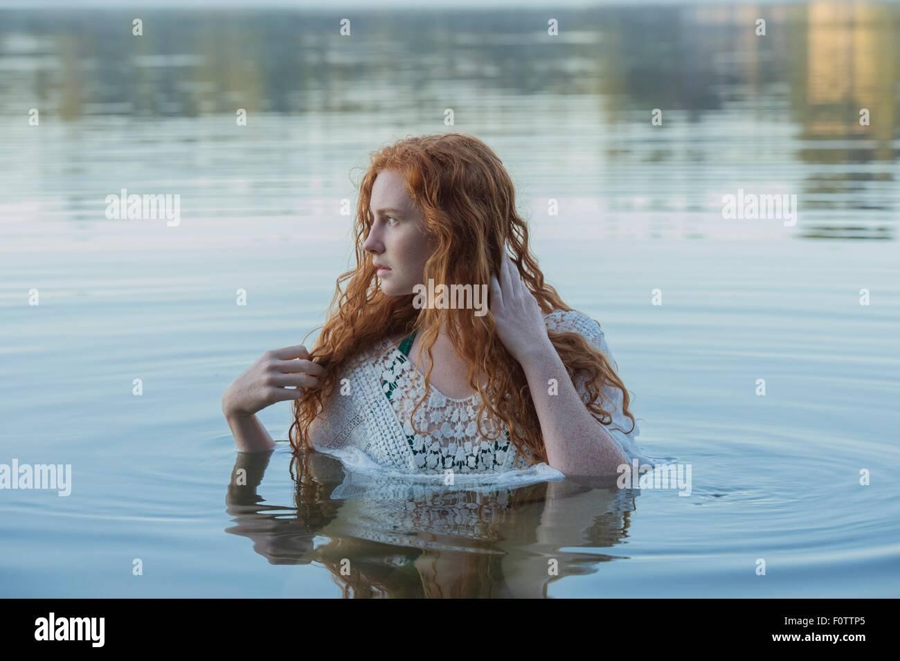 La testa e le spalle del giovane donna con lunghi capelli rossi nel lago guardando lateralmente Immagini Stock