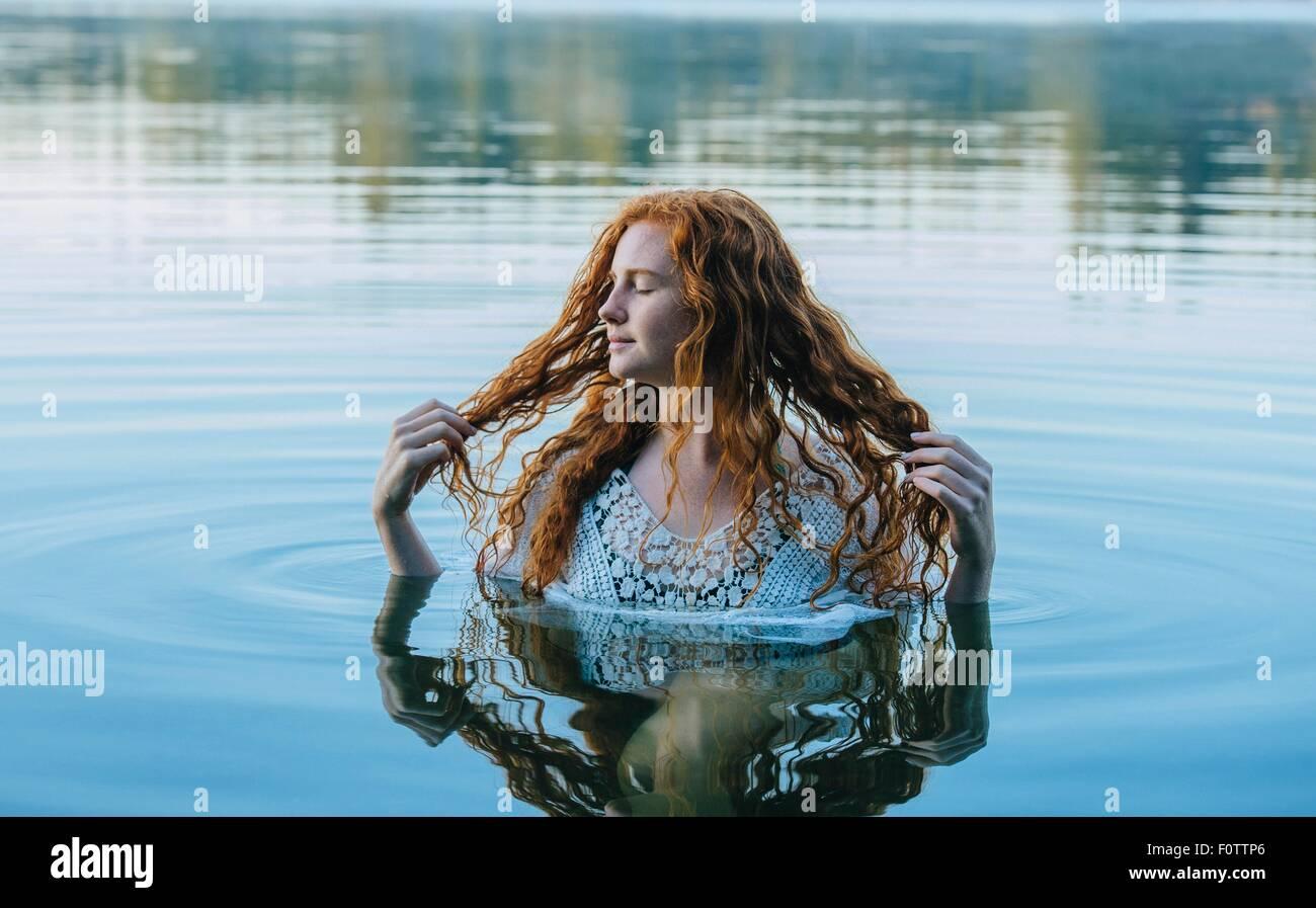La testa e le spalle del giovane e bella donna con lunghi capelli rossi nel lago Immagini Stock