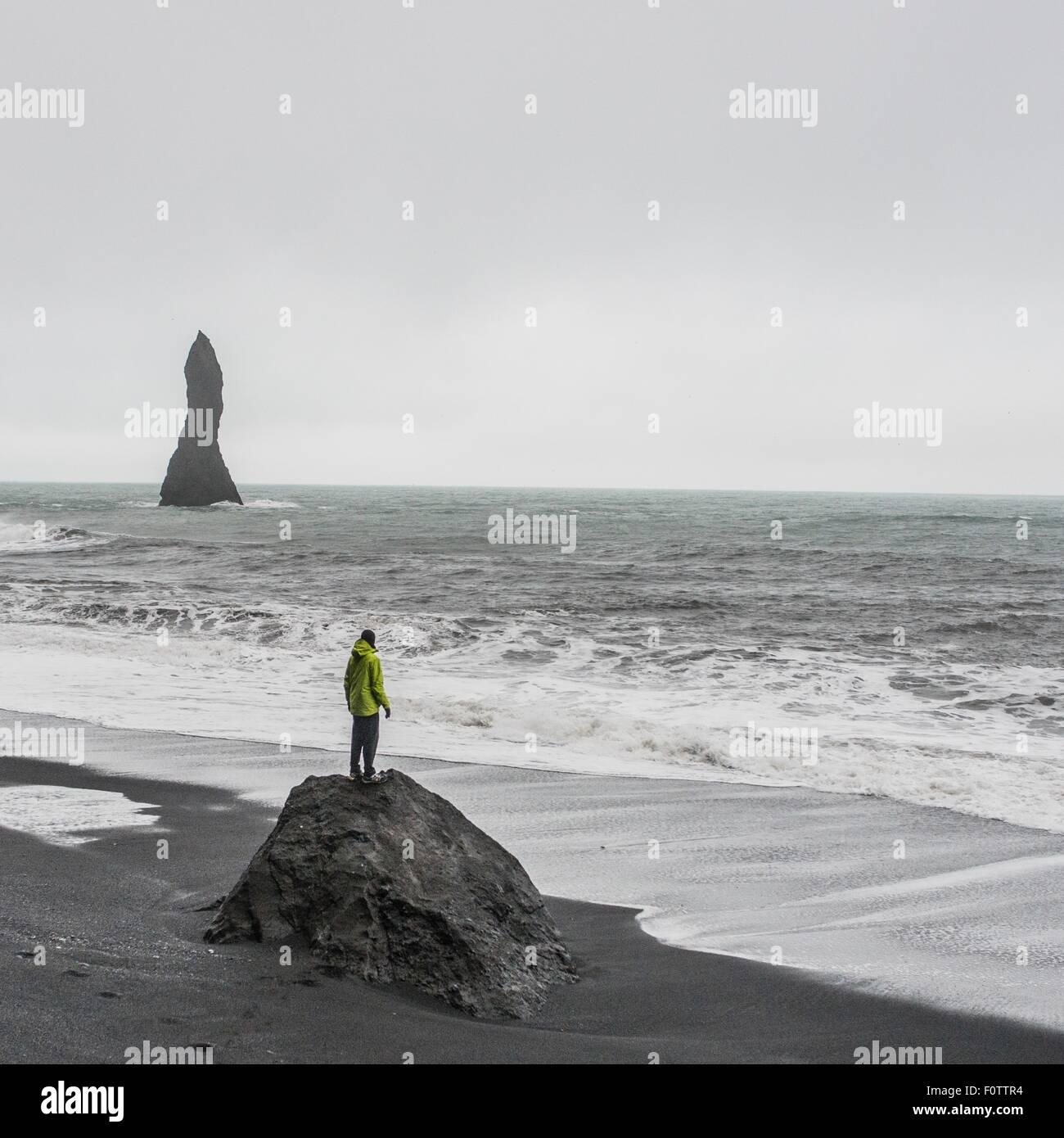 Giovane maschio per turisti in cerca del mare dalla formazione di roccia, Reynisfjara, Islanda Immagini Stock
