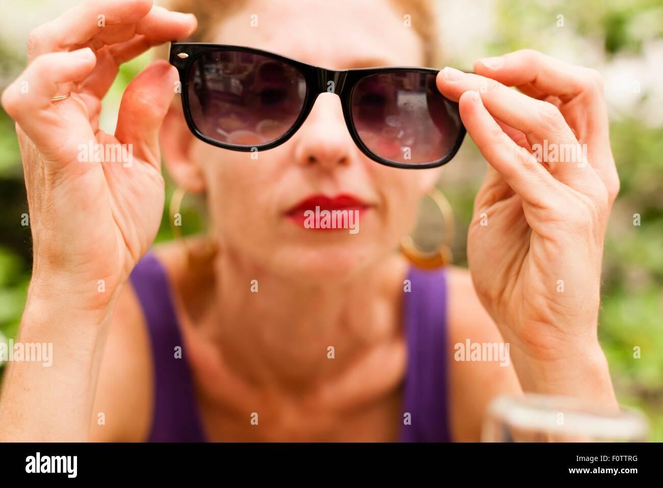 Metà donna adulta holding occhiali da sole di fronte ai suoi occhi Foto Stock