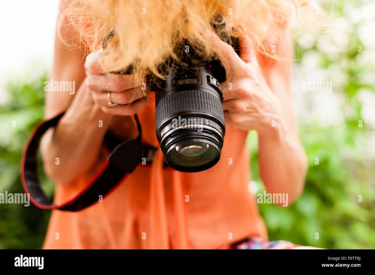 Ritagliato colpo di donna con capelli rossi a fotografare verso il basso con la reflex digitale Immagini Stock