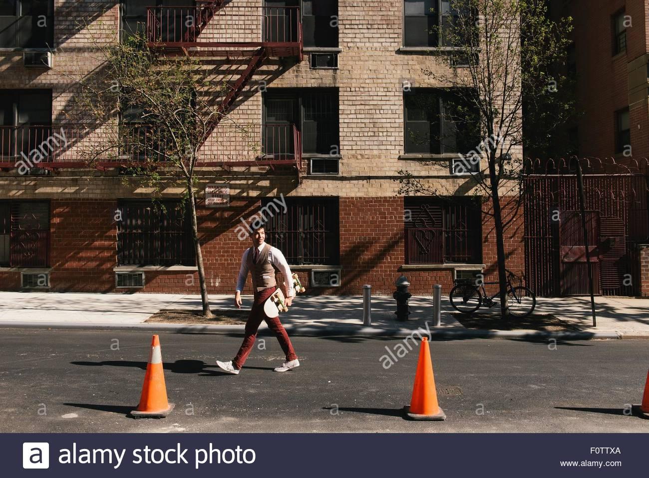 Maschio elegante guidatore di skateboard camminando lungo la strada, West Village, Manhattan STATI UNITI D'AMERICA Immagini Stock