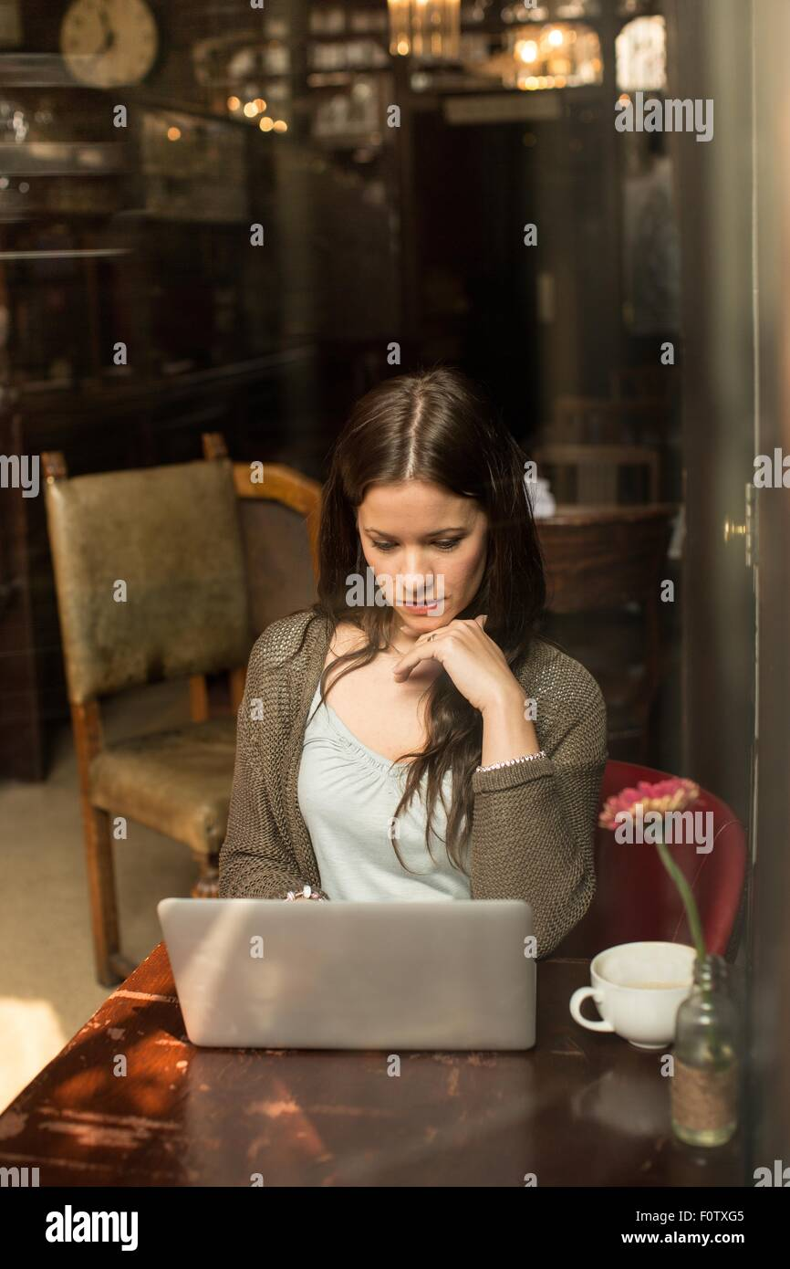 Metà donna adulta seduta a tavola utilizzando laptop, mano sul mento Foto Stock