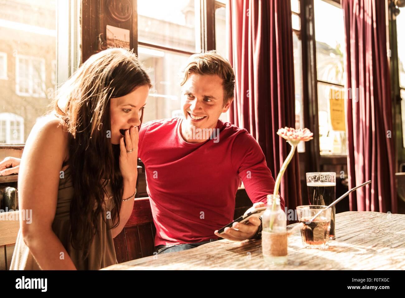 Giovane utilizza lo smartphone insieme, mano bocca di copertura Immagini Stock