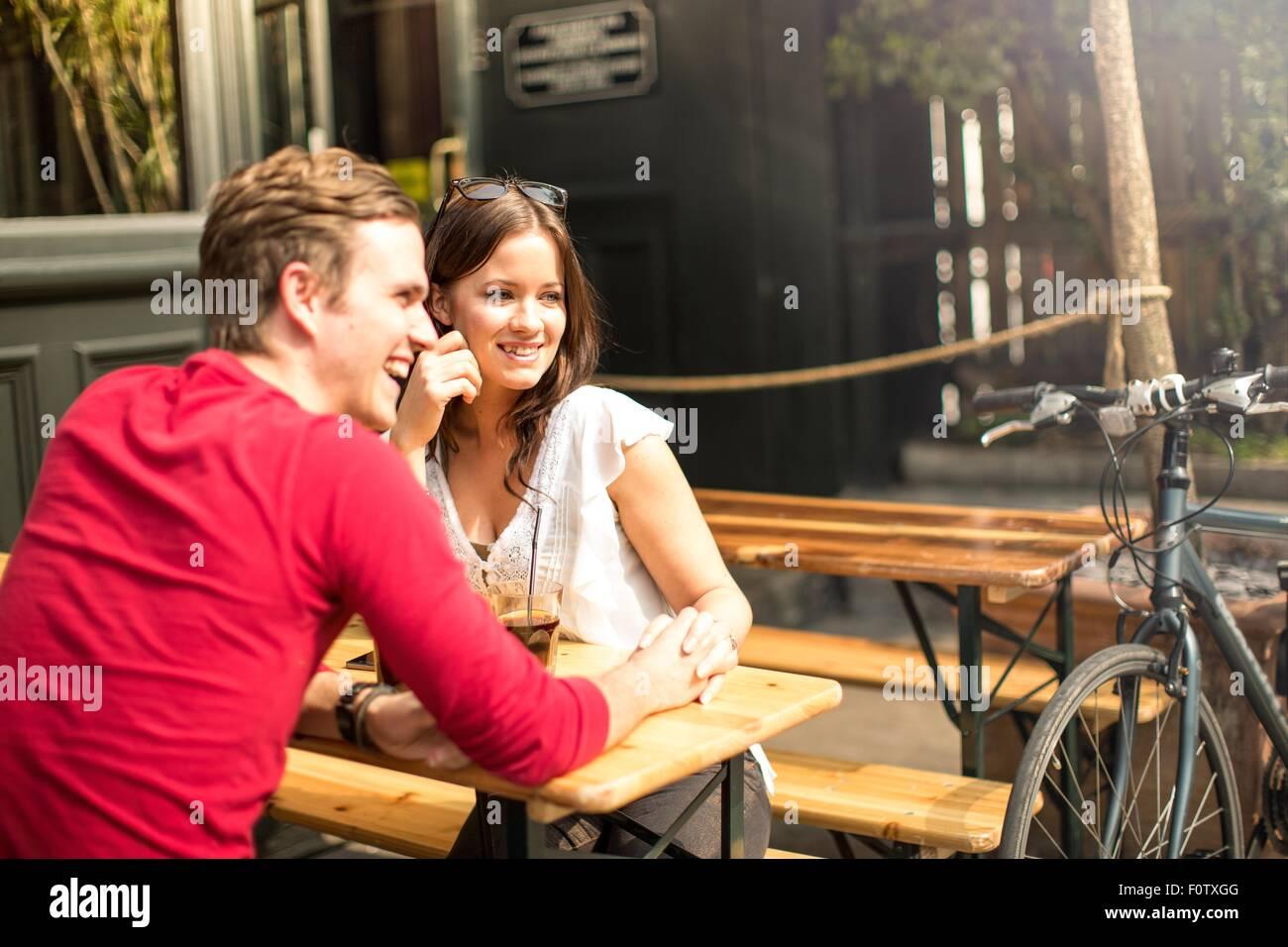 Giovane seduto faccia a faccia nel giardino della birra tenendo le mani Immagini Stock