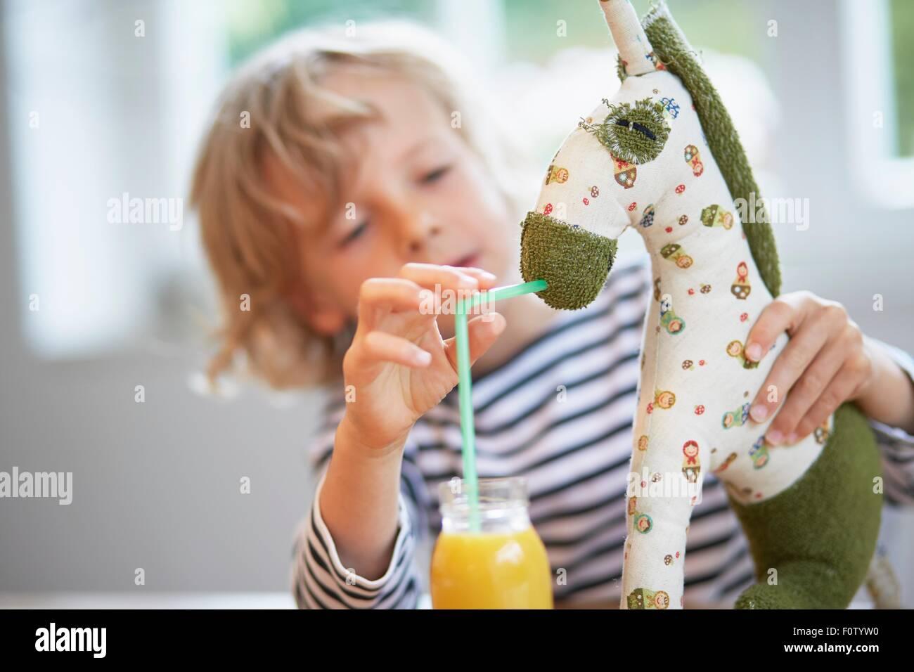 Ragazzo giovane fingendo di bevanda di alimentazione al giocattolo morbido Immagini Stock