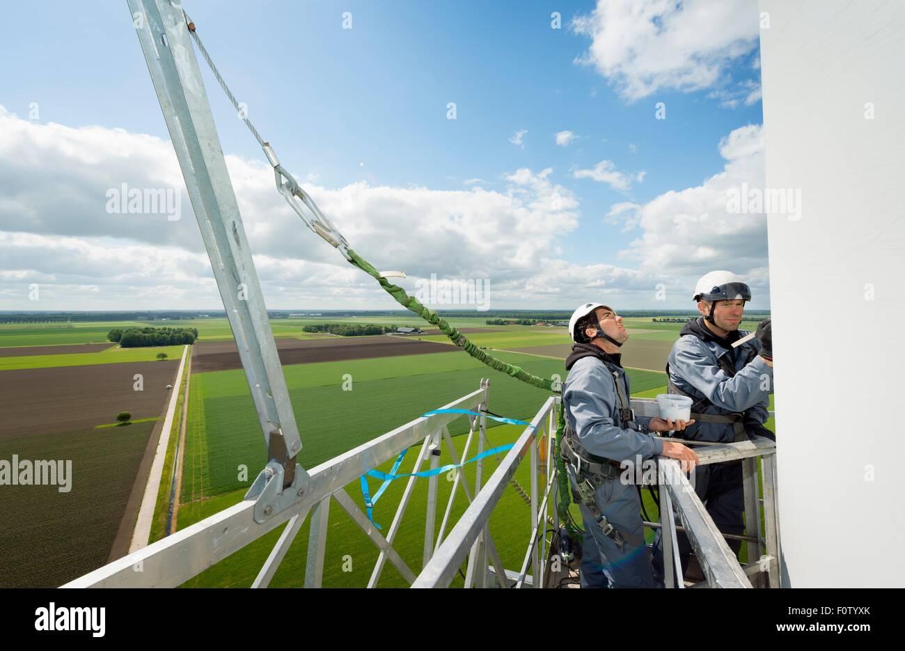 I lavori di manutenzione sulle palette di una turbina eolica Immagini Stock