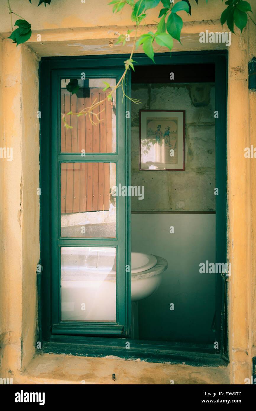 Aprire parzialmente vecchia finestra con vista parziale del lavabo senza persone Immagini Stock