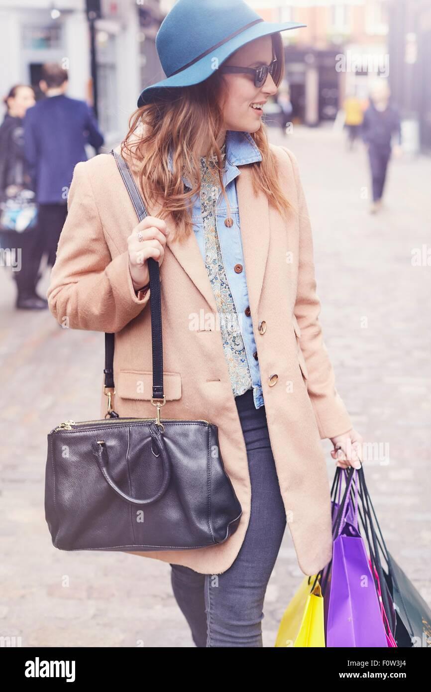 Elegante giovane femmina shopper guardando sopra la sua spalla, London, Regno Unito Immagini Stock