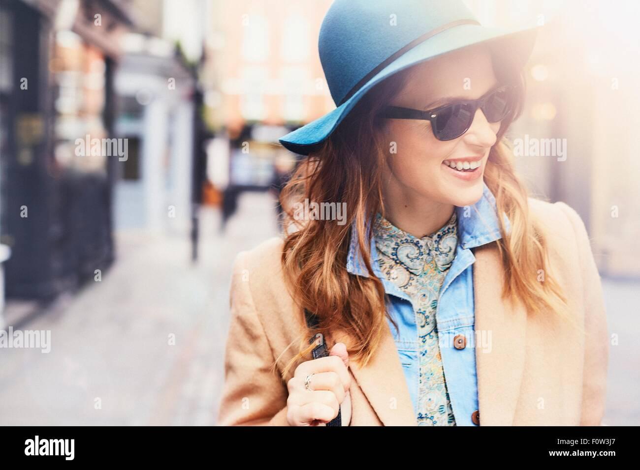 Moda giovane femmina shopper feltro che indossa un cappello e occhiali da sole, London, Regno Unito Immagini Stock