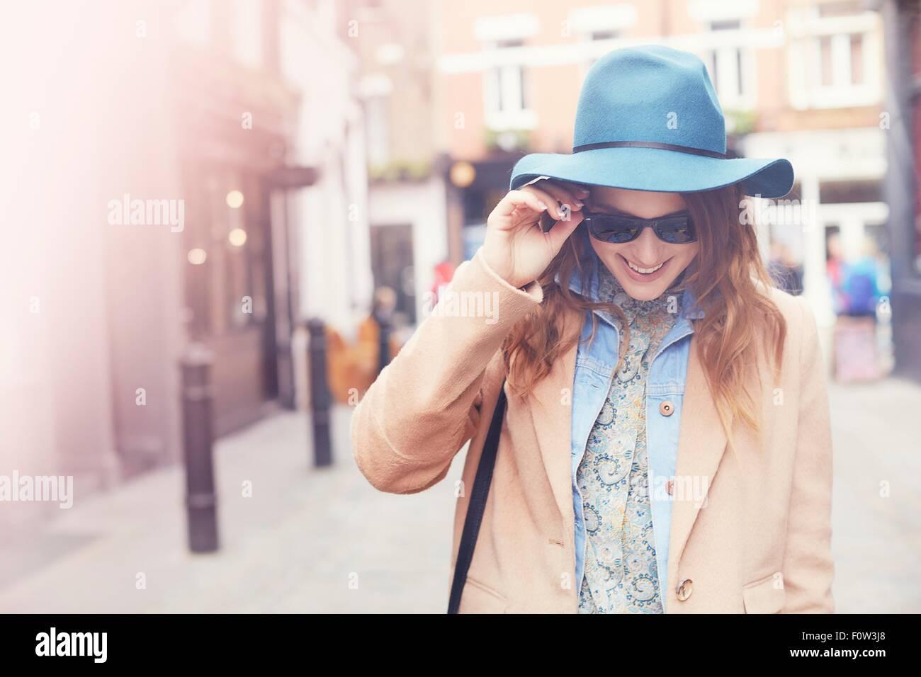 Moda giovane femmina shopper indossando occhiali da sole, London, Regno Unito Immagini Stock