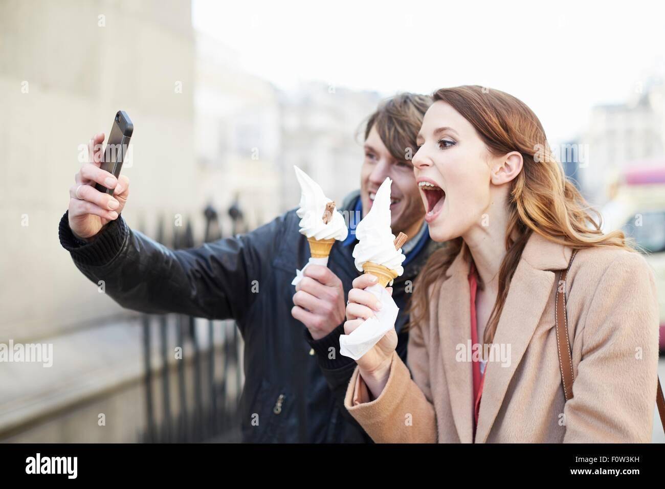 Coppia con coni gelato tenendo selfie smartphone, London, Regno Unito Immagini Stock