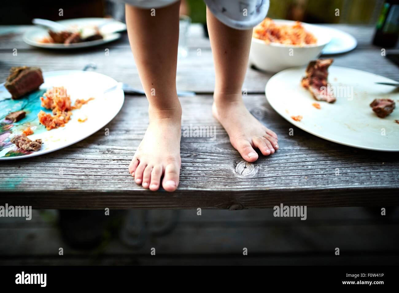 Ragazzo in piedi sul tavolo di legno Immagini Stock