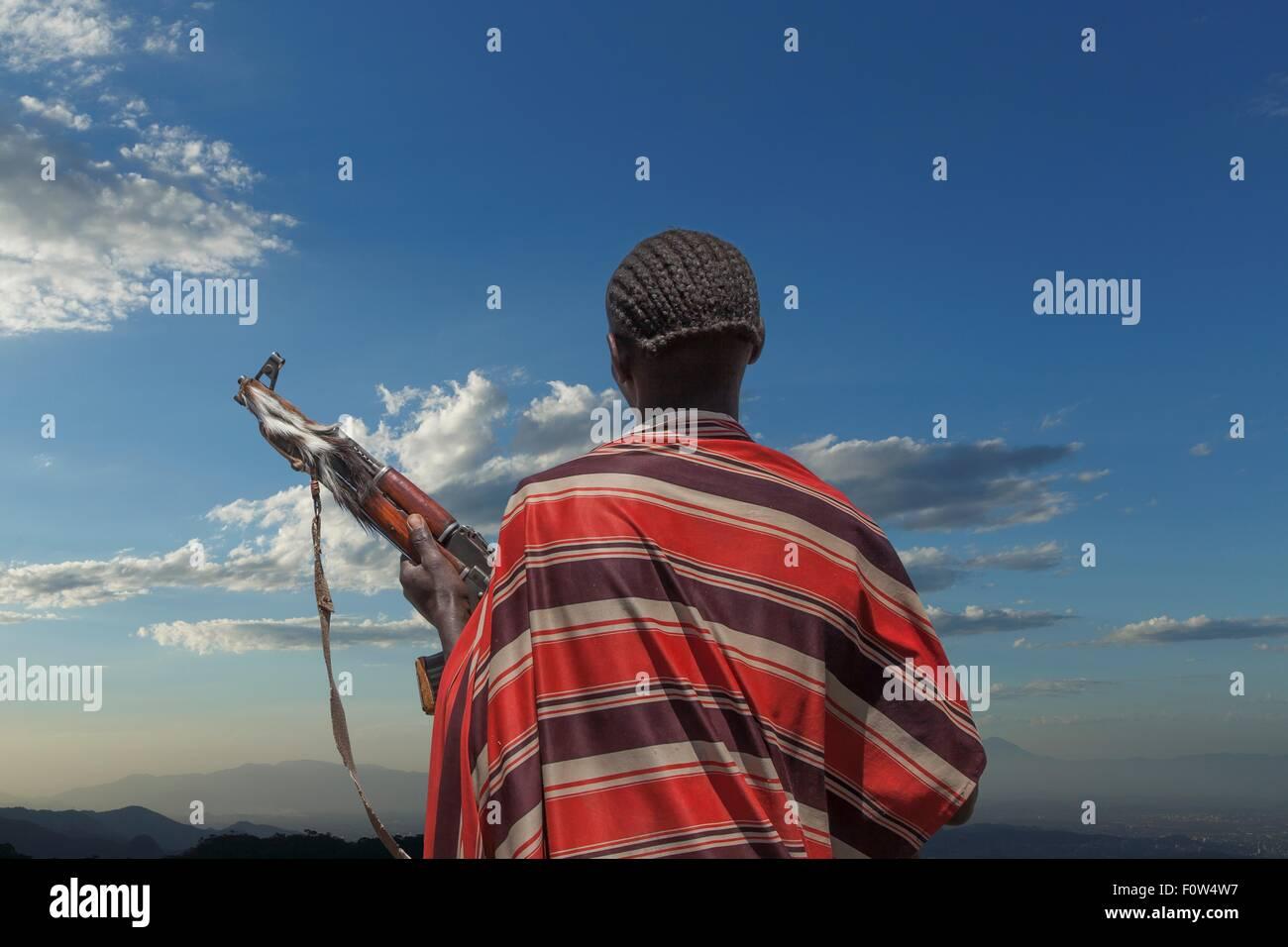 Vista posteriore del giovane di Karo tribù con fucile Kalashnikov, guardando la sua mandria , Etiopia, Africa Immagini Stock