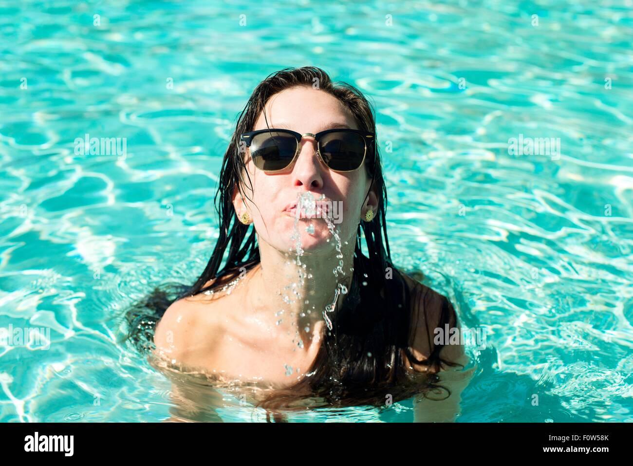 Ritratto di giovane donna in piscina schizzare acqua dalla bocca Immagini Stock