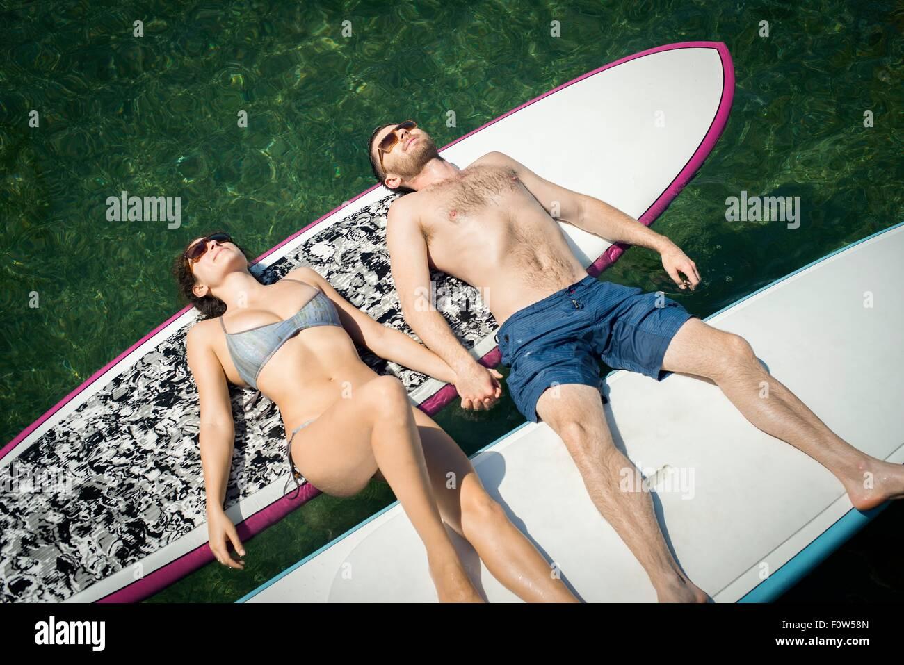 Vista aerea della coppia giovane a prendere il sole sul paddleboards Immagini Stock