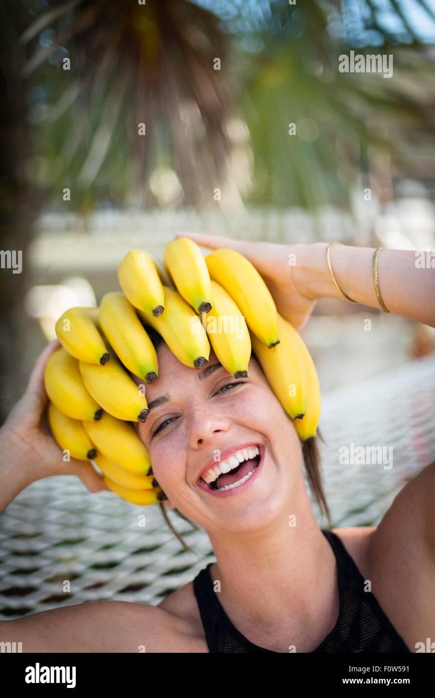 Ritratto di giovane donna in spiaggia con le banane in testa, Islamorada, Florida, Stati Uniti d'America Immagini Stock