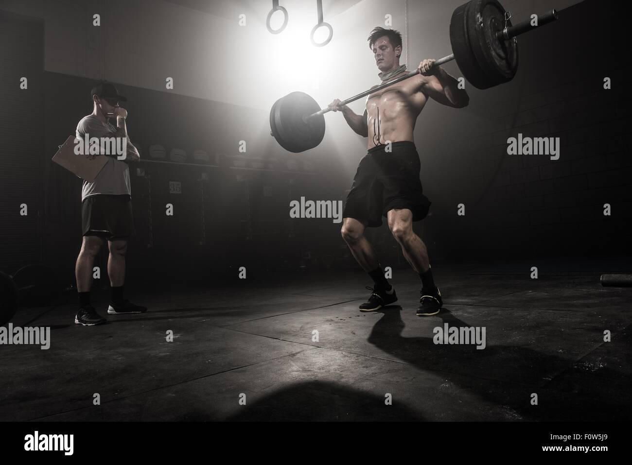 Metà uomo adulto il sollevamento barbell, mentre il trainer guarda a basso angolo di visione Immagini Stock