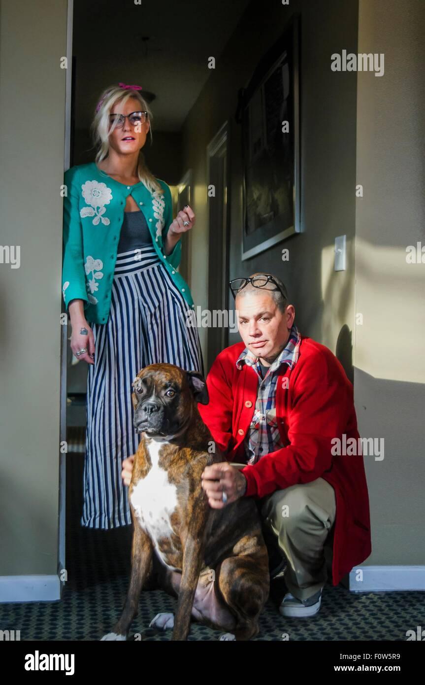 Matura in corridoio con cane boxer guardando la fotocamera Immagini Stock