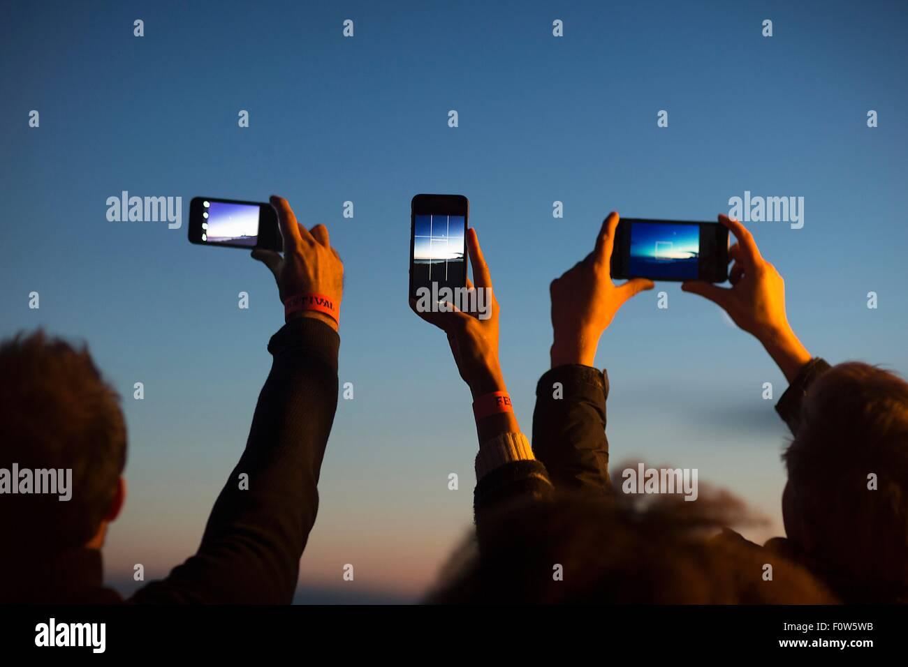 Gli amici di prendere foto con lo smartphone al crepuscolo Immagini Stock