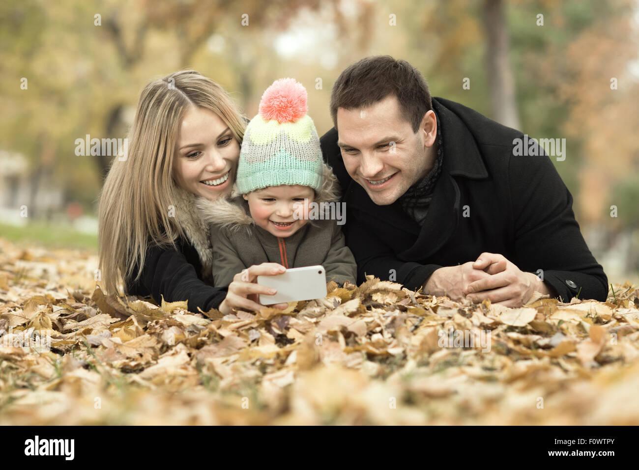 La famiglia felice con bambino prendere Selfie sul telefono, gita in autunno park Immagini Stock